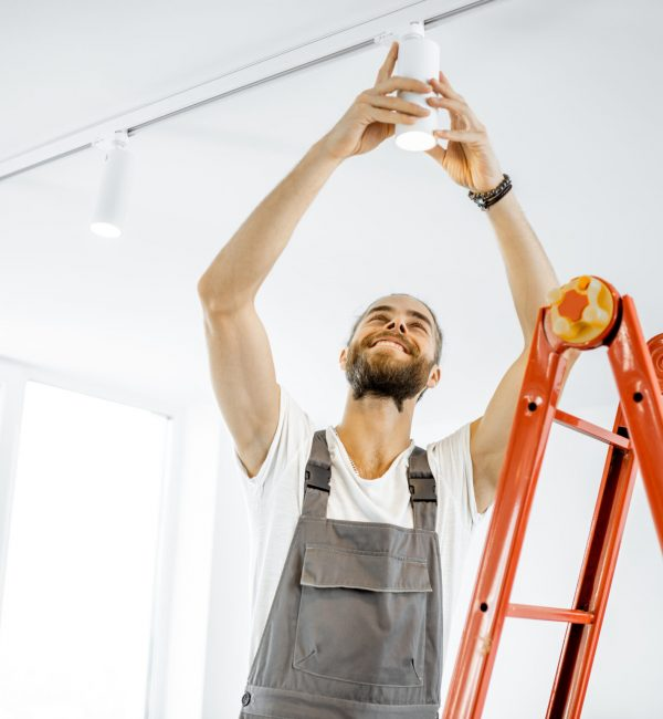 Repairman or professional electrician in workwear installing light spots, standing on the ladder in the white living room